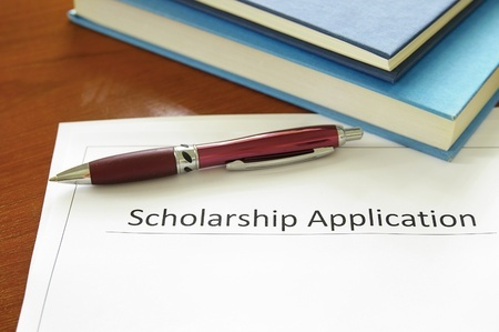 Pen and scholarship application with books